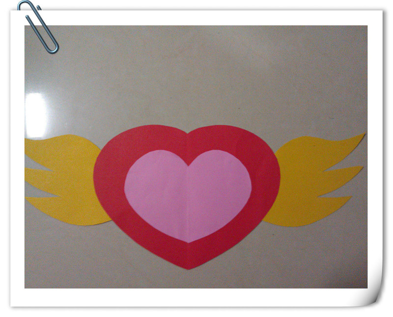 2,在卡纸上剪下最大的爱心形状,剪下一个粉色的爱心形状,剪下两个翅膀